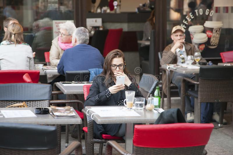 Budapest, Hungary - April 8, 2018: Beautiful girl writes a text message on your phone while sitting in coffee shop royalty free stock image