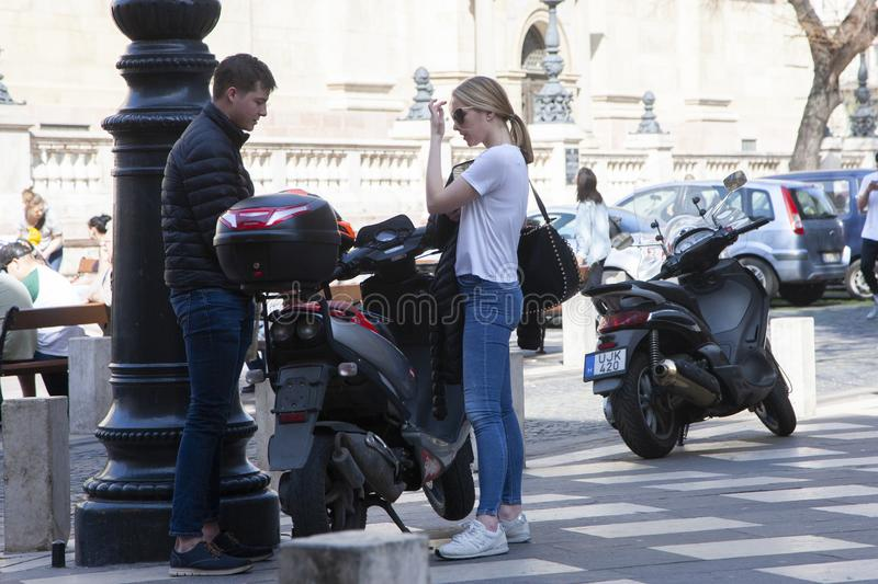 Budapest, Hungary - April 9, 2018: Full length portrait of a young attractive couple standing on a city street near motorbike stock photo