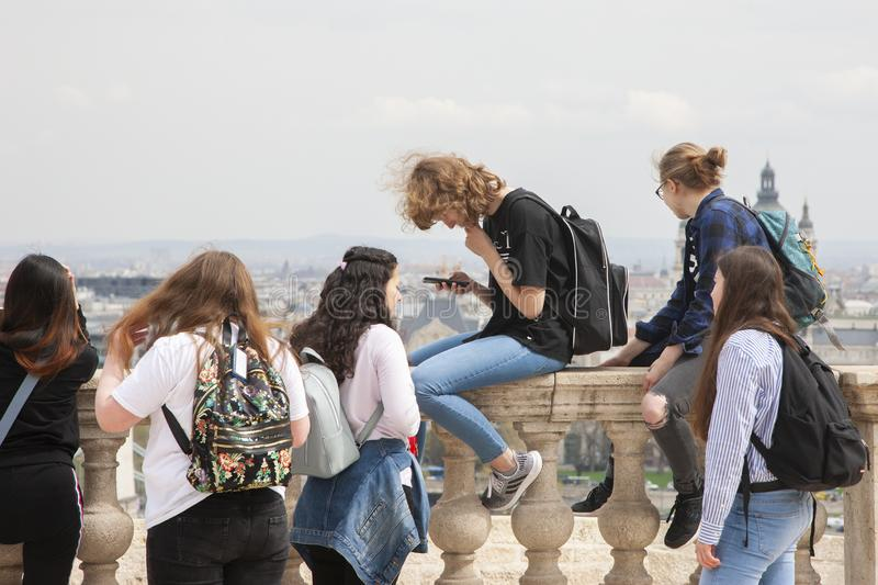 Budapest, Hungary - April 10, 2018: Group of happy smiling carefree young stylish girls communicate against the background of the stock photography