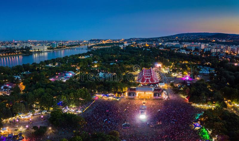 BUDAPEST, HUNGARY - AUGUST 12, 2018: Aerial panoramic photograph of Sziget Festival and main stage. With the skyline of Budapest at background at blue hour stock photo