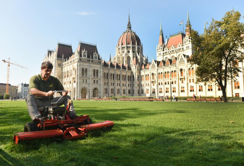 Budapest, Hungari - August 29, 2017: Worker mowing grass near Hungarian Parliament Building in Budapest. royalty free stock images