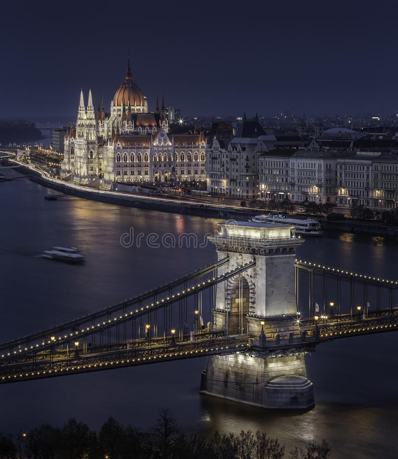 Budapest, Hungary - Beautiful illuminated Szechenyi Chain Bridge with the Parliament of Hungary at blue hour. With sightseeing boat on River Danube royalty free stock images