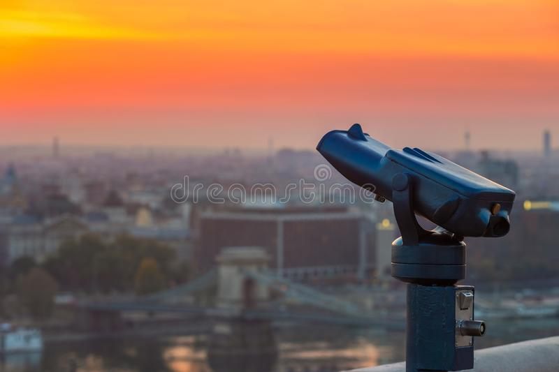 Budapest, Hungary - Blue binoculars with the view of Pest with Szechenyi Chain Bridge and beautiful golden sky. At sunrise royalty free stock photo