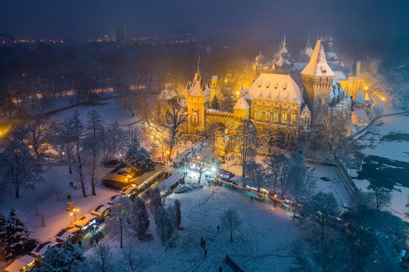 Budapest, Hungary - Christmas market in snowy City Park Varosliget from above at night with snowy trees and Vajdahunyad royalty free stock images