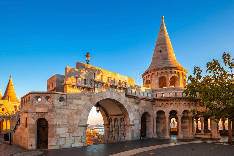 Budapest, Hungary - Entrance and tower of the famous Fisherman`s Bastion on a golden autumn sunrise. With Parliament of Hungary at the background and clear blue royalty free stock photo