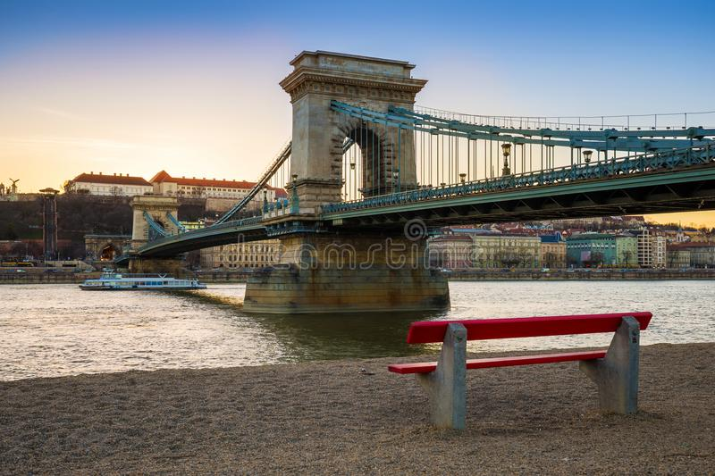 Budapest, Hungary - Famous Szechenyi Chain Bridge with traditional red bench and sightseeing boat on River Danube. At sunset. Clear blue sky royalty free stock photography