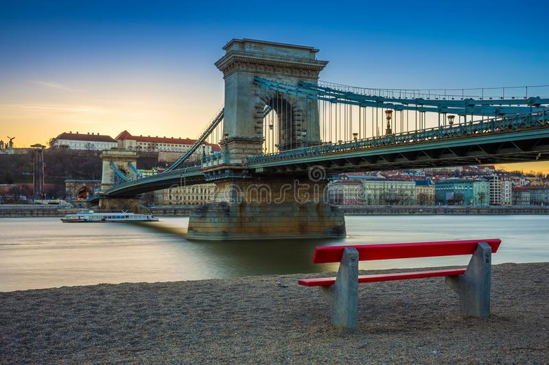 Budapest, Hungary - Famous Szechenyi Chain Bridge with traditional red bench and sightseeing boat. On River Danube at sunset. Clear blue sky stock images