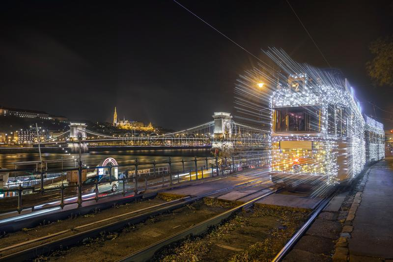 Budapest, Hungary - Festively decorated light tram fenyvillamos on the move with Szechenyi Chain Bridge, Matthias Church. And Fisherman`s Bastion by night stock photos