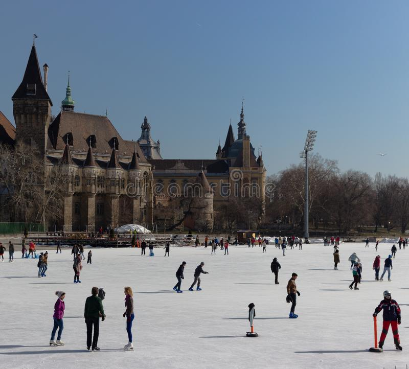 Budapest, Hungary - 02/19/2018: ice rink with people against old castle in Varoshelighet park. Winter sport and fun. royalty free stock photography