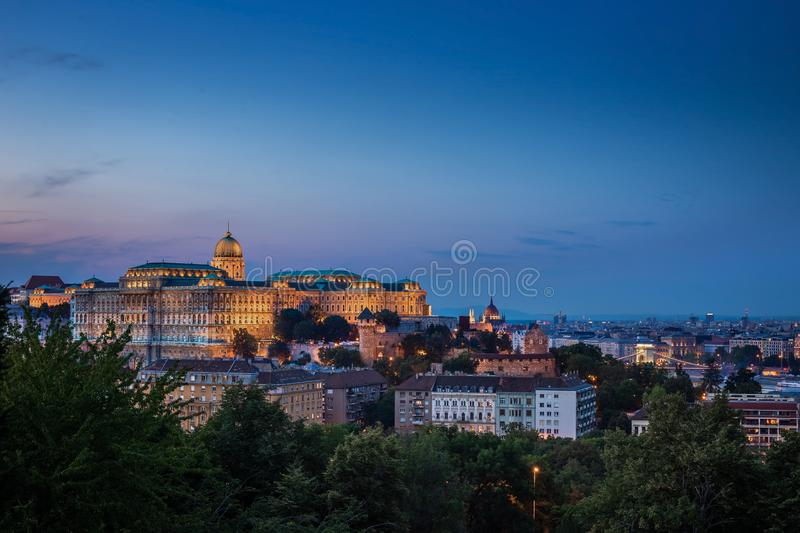 Budapest, Hungary - Illuminated Buda Castle Royal Palace with Parliament of Hungary and Szechenyi Chain Bridge. At blue hour on a summer night royalty free stock photo