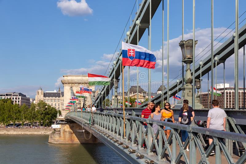Pedestrians at Budapest chain bridge with Slovak and Hungarian flags. Budapest, Hungary - Juli 10, 2019: Pedestrians at Budapest chain bridge with Slovak and royalty free stock photography