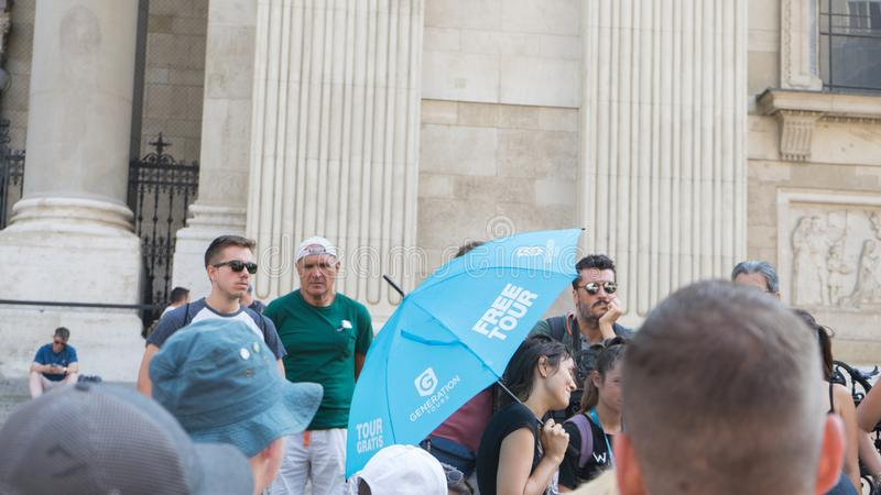 Budapest / Hungary - July 29 2019: Free walking tours guide in Budapest with blue umbrella talking with interested group of people royalty free stock photography