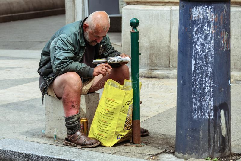 Homeless in the street of Budapest. Budapest, Hungary, July 04: a Homeless man reading a newspaper sitting on a stone on the sidewalk of one of the streets of stock image