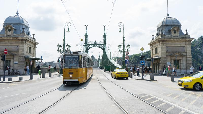 Budapest / Hungary - July 29 2019: Liberty Bridge or Freedom Bridge and yellow train in Budapest, Hungary. Cars crossing in the stock image