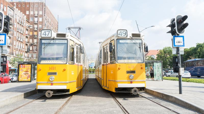 Budapest / Hungary - July 29 2019: Two yellow retro tramways stop in the station to take the passengers in the center avenue of stock photos