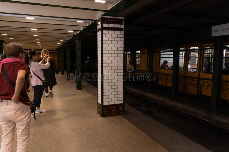 Budapest, Hungary - May 2019: Chinese tourist taking pictures on the station of Budapest subway M1 yellow line stock photo