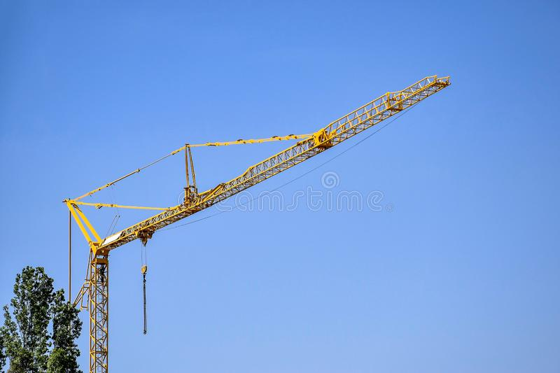 BUDAPEST, HUNGARY - MAY 2019: High-rise industrial crane against blue sky and green trees. Modern civil engineering. Construction royalty free stock photography