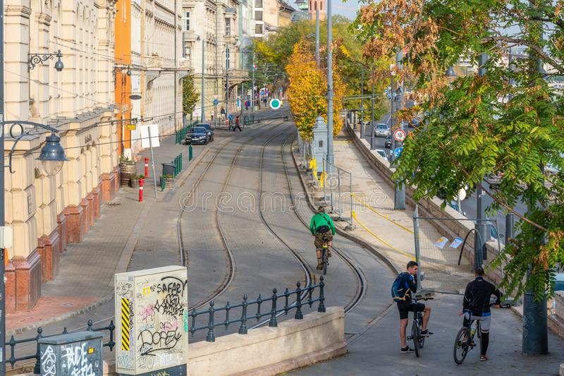 BUDAPEST, HUNGARY - October 25, 2018: Tram rails, random cyclists and buildings royalty free stock images