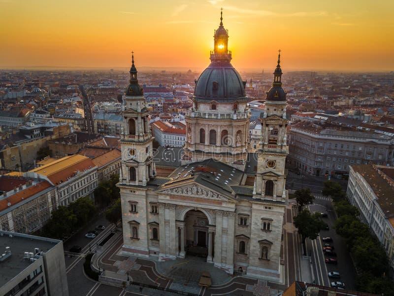 Budapest, Hungary - The rising sun shining through the tower of the beautiful St.Stephen`s Basilica Szent Istvan Bazilika. At sunrise on an aerial shot stock photos