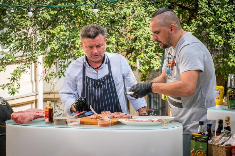 Two caucasian male shefs in Budapest Hungary who prepares a meat dish, Outdoor cooking. stock photo