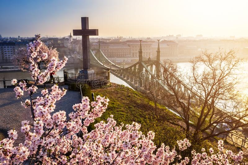 Budapest, Hungary - Spring has arrived in Budapest with beautiful Cherry Blossom, cross and Liberty Bridge. On a sunny morning stock image