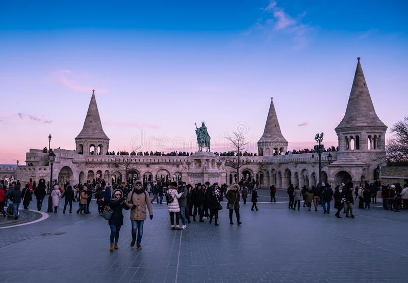 People visiting Fisherman`s Bastion at Budapest at sunset. Budapest, Hungary - Sunset at the Fisherman`s Bastion with King Stephen I statue and people visiting stock photography