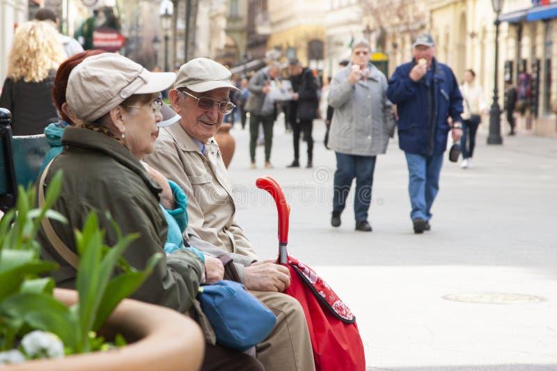Budapest, Hungría - 6 de abril de 2018: Marido maduro y esposa que gozan junto mientras que se sienta en banco en la ciudad imágenes de archivo libres de regalías