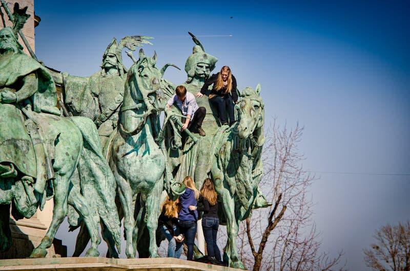Budapest, Hungría - 4 de marzo de 2012 Adolescentes que suben para arriba las estatuas en el cuadrado de los héroes, Hosok Tere fotografía de archivo libre de regalías