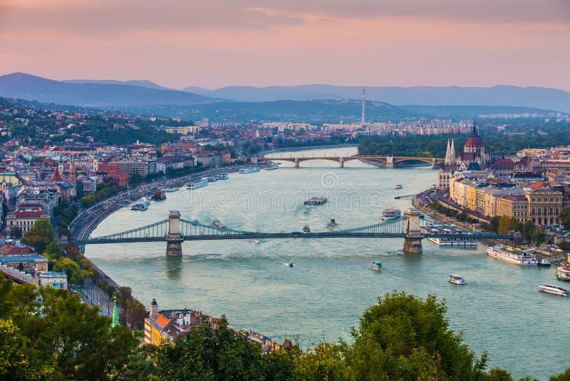 Budapest, Hungría - opinión panorámica del horizonte en la puesta del sol del puente de cadena famoso de Szechenyi foto de archivo