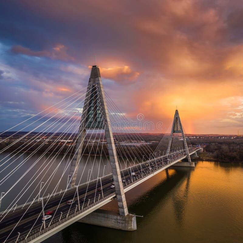 Budapest, Hungría - vista aérea del puente de Megyeri sobre el río Danubio con el cielo y nubes de oro hermosas y circulación foto de archivo libre de regalías