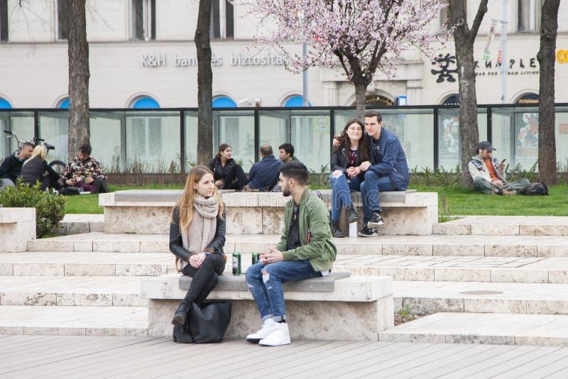 Budapest, Hungria - 5 de abril de 2018: Dois jovens que sentam-se em bancos em um parque e em uma fala imagem de stock