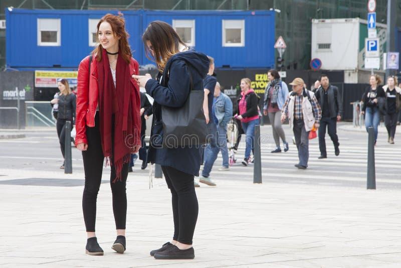 Budapest, Hungria - 5 de abril de 2018: Duas meninas bonitas que andam abaixo da rua fotografia de stock royalty free