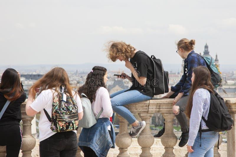 Budapest, Hungria - 10 de abril de 2018: O grupo de meninas à moda novas despreocupadas de sorriso felizes comunica-se na perspec fotografia de stock