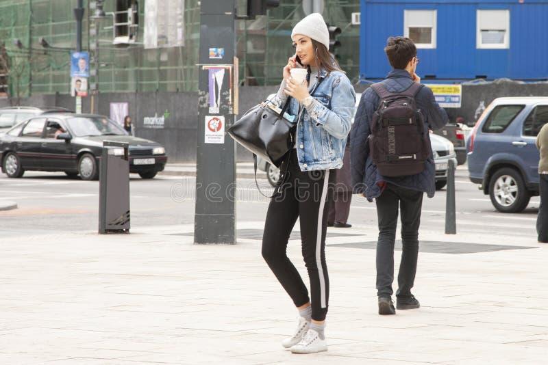 Budapest, Hungria - 5 de abril de 2018: O turista atrativo novo da mulher está na rua da cidade, smartphone dos usos e bebe o caf fotos de stock