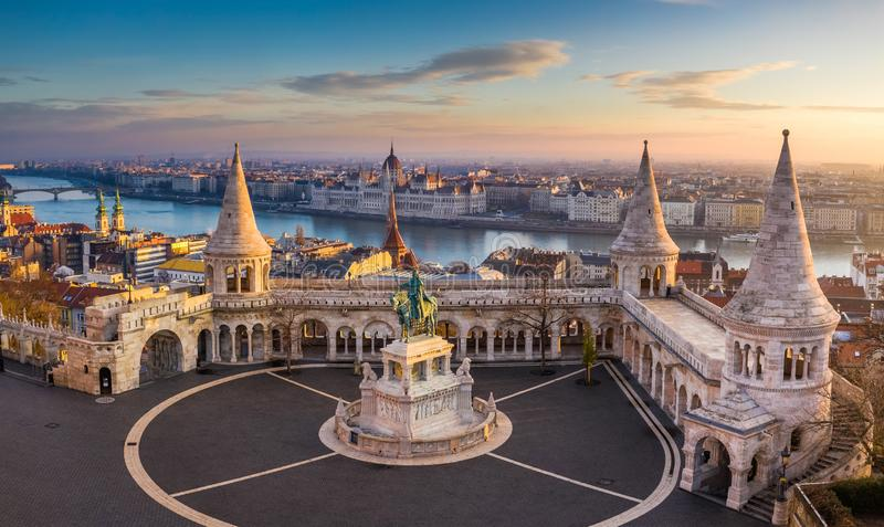 Budapest, Hungria - o bastião do pescador famoso no nascer do sol com a estátua do rei Stephen Eu e parlamento imagens de stock