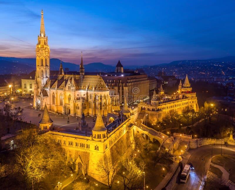 Budapest, Hungria - vista aérea do bastião Halaszbastya e Matthias Church do pescador iluminado no crepúsculo imagens de stock royalty free
