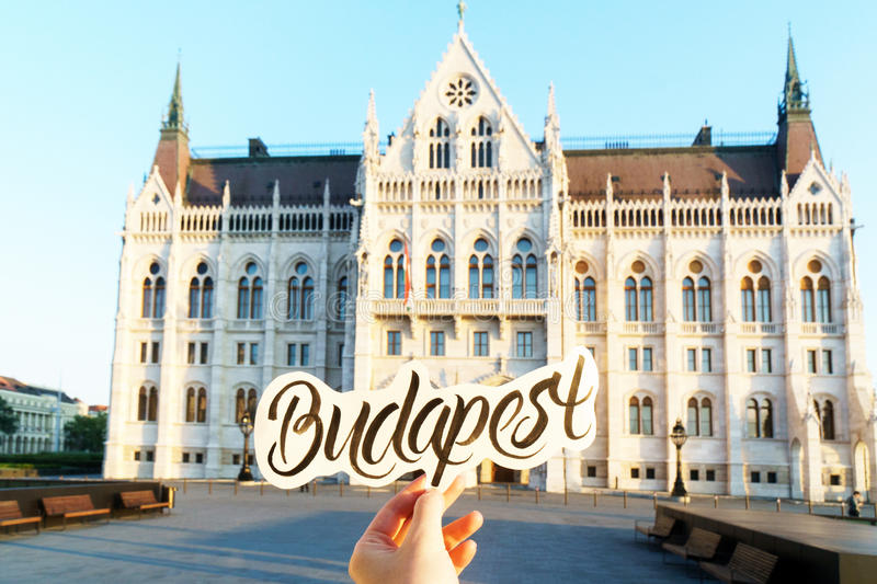 Budapest lettering sticker in a hand and Hungarian parliament building on background. Budapest lettering sticker in a hand royalty free stock photo