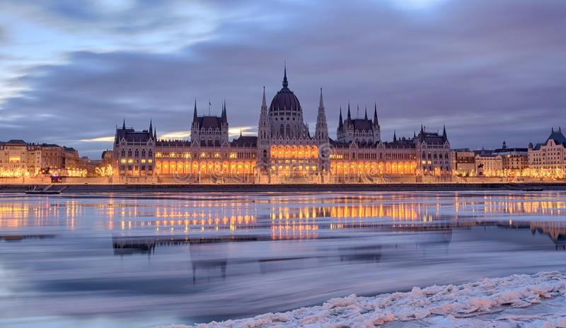 Budapest Parliament building frontal view in winter. Winter twilight view of Budapest Parliament building reflected in frozen Danube river with ice flowing stock photo