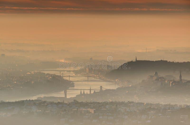 Budapest som är i stadens centrum på soluppgång i glödande vintermorgonmist royaltyfri foto