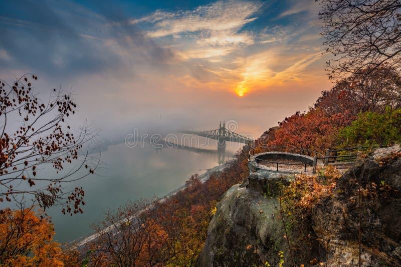Budapest, Ungarn - Ausblick auf Gellert-Hügel mit Liberty Bridge Szabadsag Hid, Nebel über Fluss Donau, bunter Himmel und Wolken stockbild