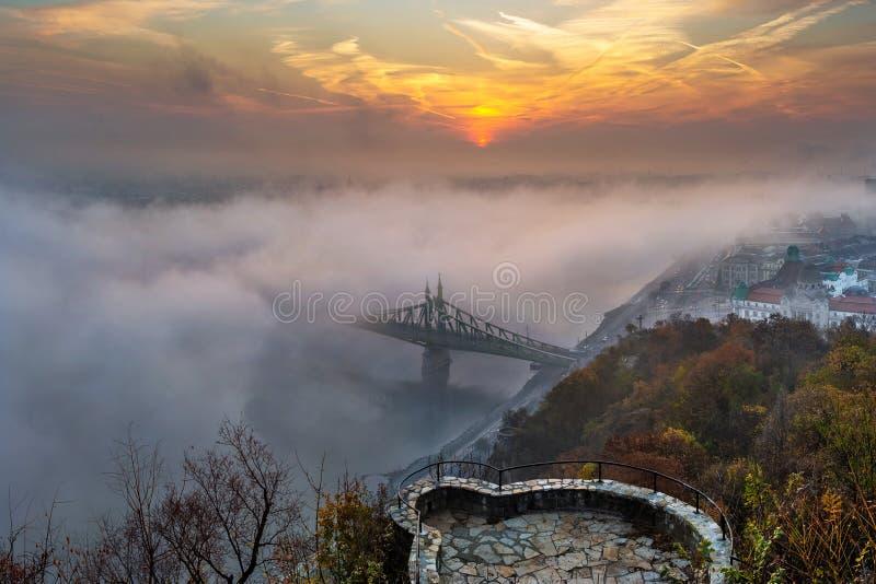 Budapest, Ungarn - mysteriöser nebeliger Sonnenaufgang mit Liberty Bridge Szabadsag versteckt und Ausblick auf Gellert-Hügel lizenzfreie stockfotos