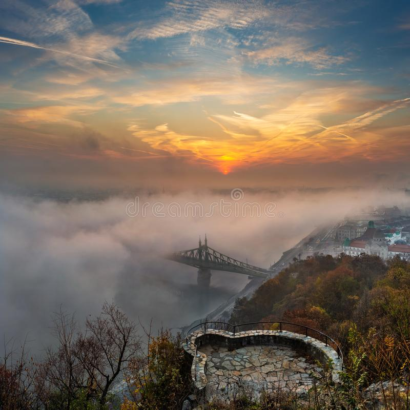 Budapest, Ungarn - mysteriöser nebeliger Sonnenaufgang mit Liberty Bridge Szabadsag versteckt und Ausblick auf Gellert-Hügel stockbilder