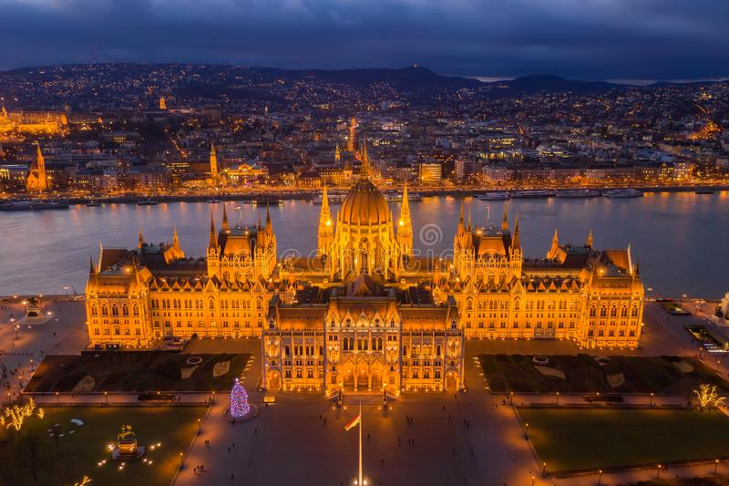 Budapest, Ungarn - Vogelperspektive des belichteten ungarischen Parlamentsgebäudes an der goldenen Stunde mit Weihnachtsbaum lizenzfreies stockbild