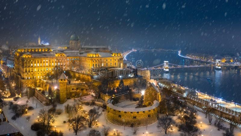 Budapest, Ungarn - Vogelperspektive von belichtetem Buda Castle Royal Palace auf einer Winternacht mit dem schweren Schneien stockbild