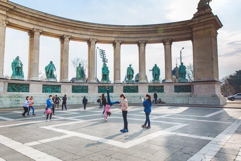BUDAPEST UNGERN - APRIL 04, 2019: Många turister strosar på hjältarnas fyrkant Är en av debesökte dragningarna royaltyfria foton