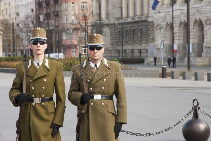 Budapest Ungern - April 6, 2018: Medlemmar av den ungerska hedersvakten som marscherar runt om den hissade ungerska flaggan nära royaltyfri fotografi