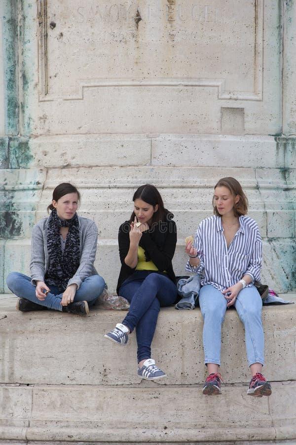 Budapest Ungern - April 10, 2018: Två ungdomarsom sitter på bänkar i, parkerar och samtal royaltyfri foto