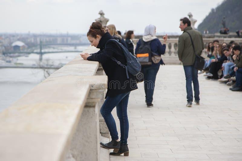 Budapest Ungern - April 10, 2018: Unga kvinnor koncentrerade blickar på mobiltelefonskärmen fotografering för bildbyråer