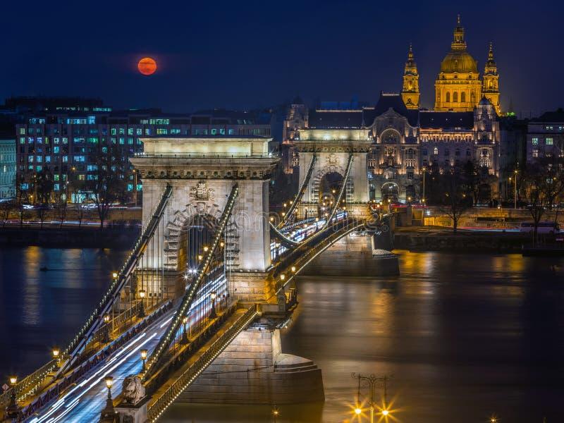 Budapest Ungern - blodm?ne som stiger ?ver centrum av Budapest med den h?rliga Szechenyi kedjebron och Sts Stephen basilika royaltyfri bild