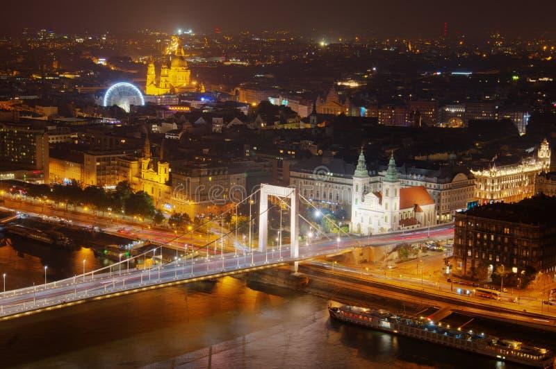 Budapest, Ungern, den Eleazabetina bron, kyrkan av St Stephan och Ferris Wheel, Danube River - nattbild royaltyfri bild